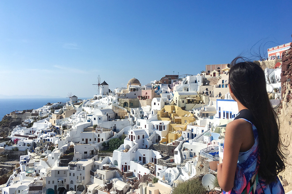 Eryn looks out to the whitewashed buildings spread across the hillside in Oia, Santorini, Greece