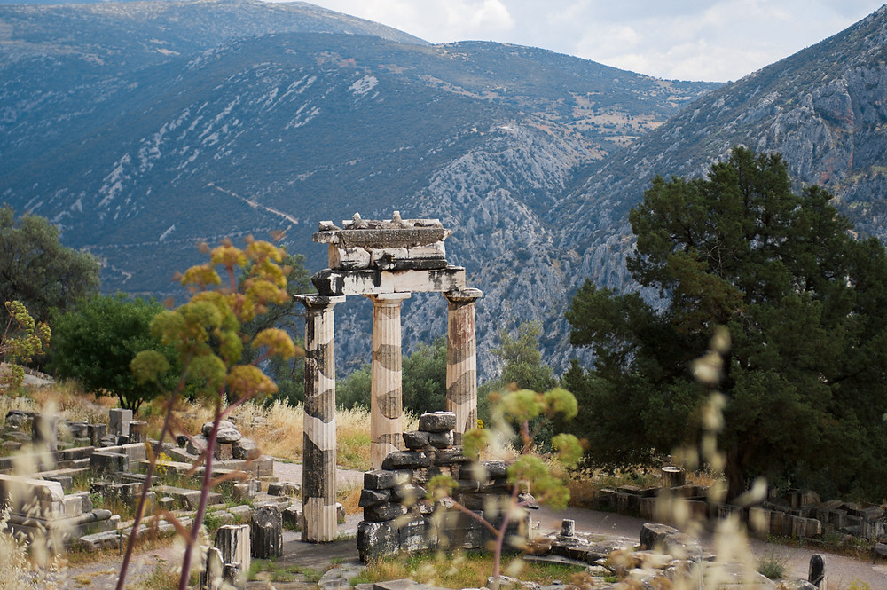 The ruins of the Tholos of Delphi and the mountains in Delphi, Greece in the distance