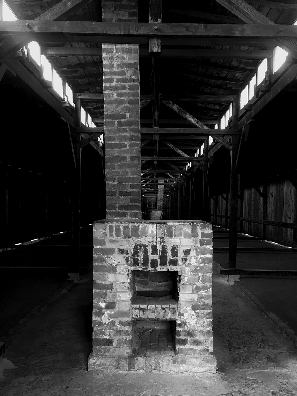 Dark black and white photography featuring a cubic fireplace with a chimney going through the roof of a wooden barrack at Auschwitz II