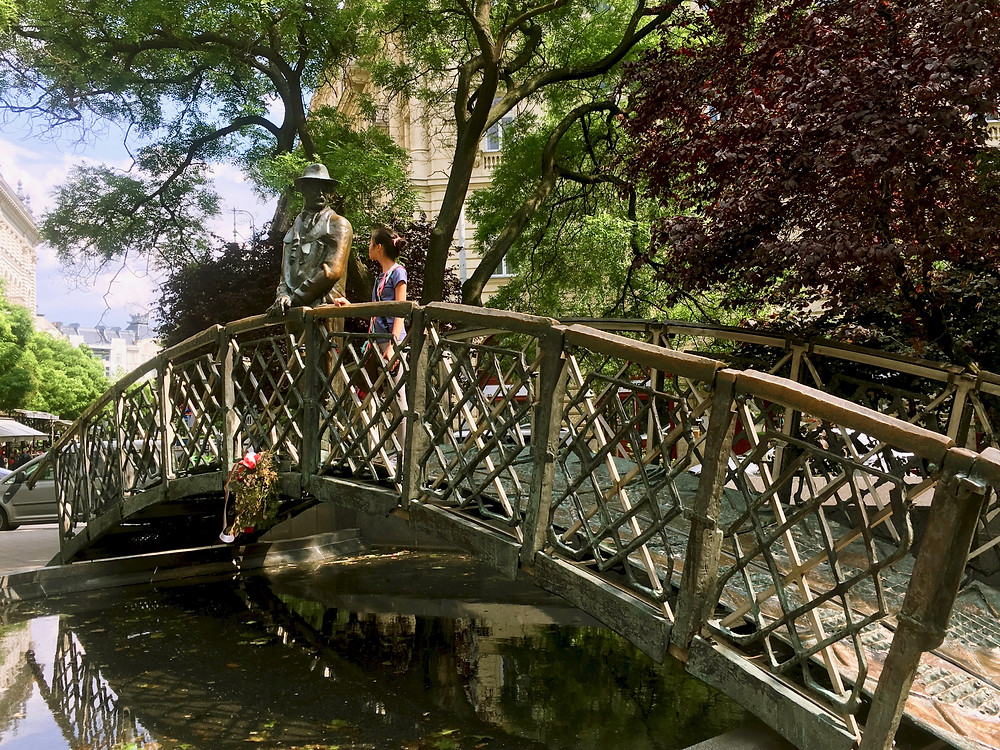 Eryn stands next to a statue of Imre Nagy on a small bridge under the shade of trees in Budapest, Hungary