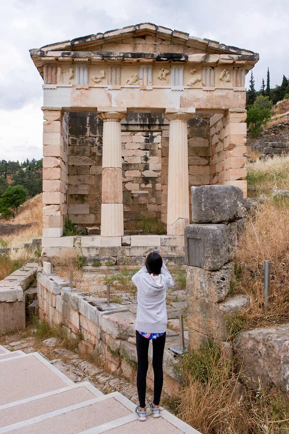 Eryn stands in front of the Athenian Treasury building to take a photo of it