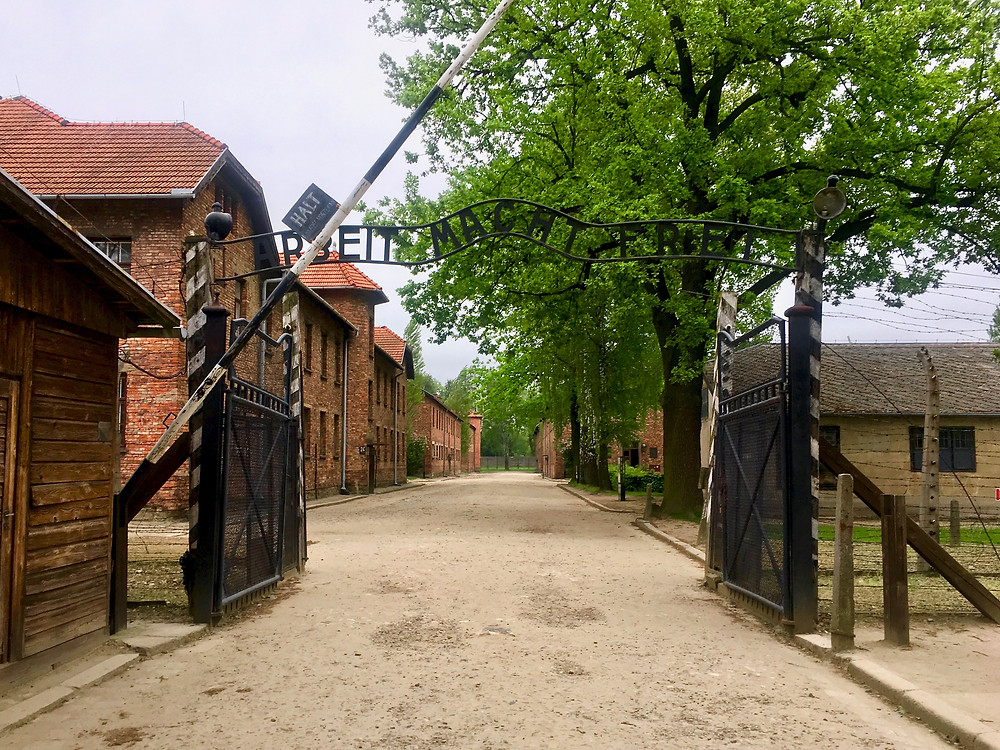 "A open black gate with metal cut out in the words ""Arbeit Macht Frei"" in front of a dirt path and brick structures of Auschwitz I"