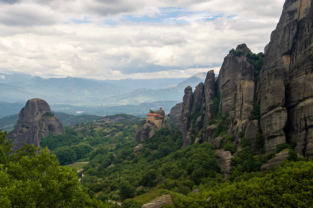 A monastery in Meteora, Greece beside rock cliffs surrounded by lush greenery and hills in the distance