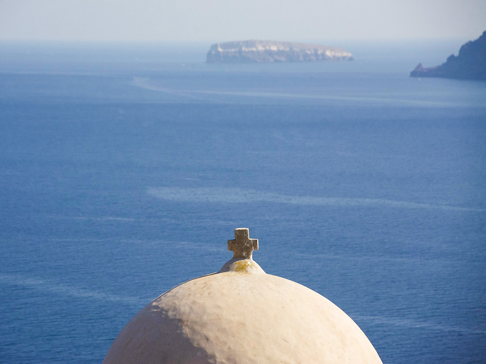 A brown domed roof with a small cross on top in front of a view of the open ocean and some distant islands of Santorini, Greece