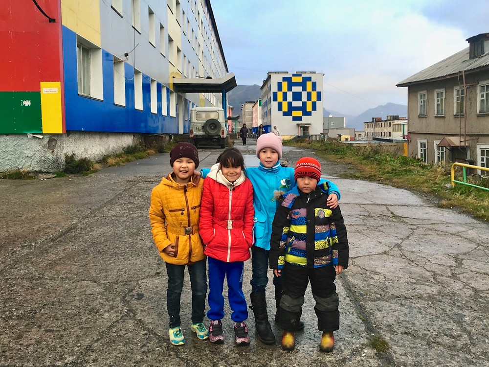 Four kids in colorful jackets stand together for a photo in Provideniya, Russia