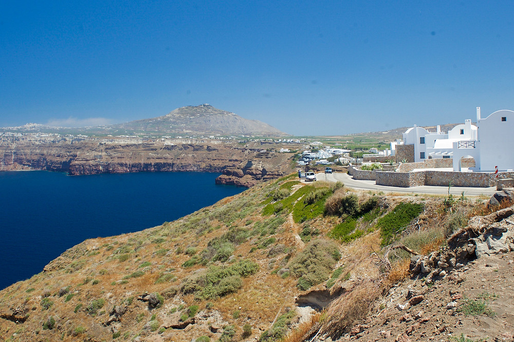 Rocks and cliffs covered in shrubs and some whitewashed buildings on the side surround a deep blue ocean in Santorini, Greece