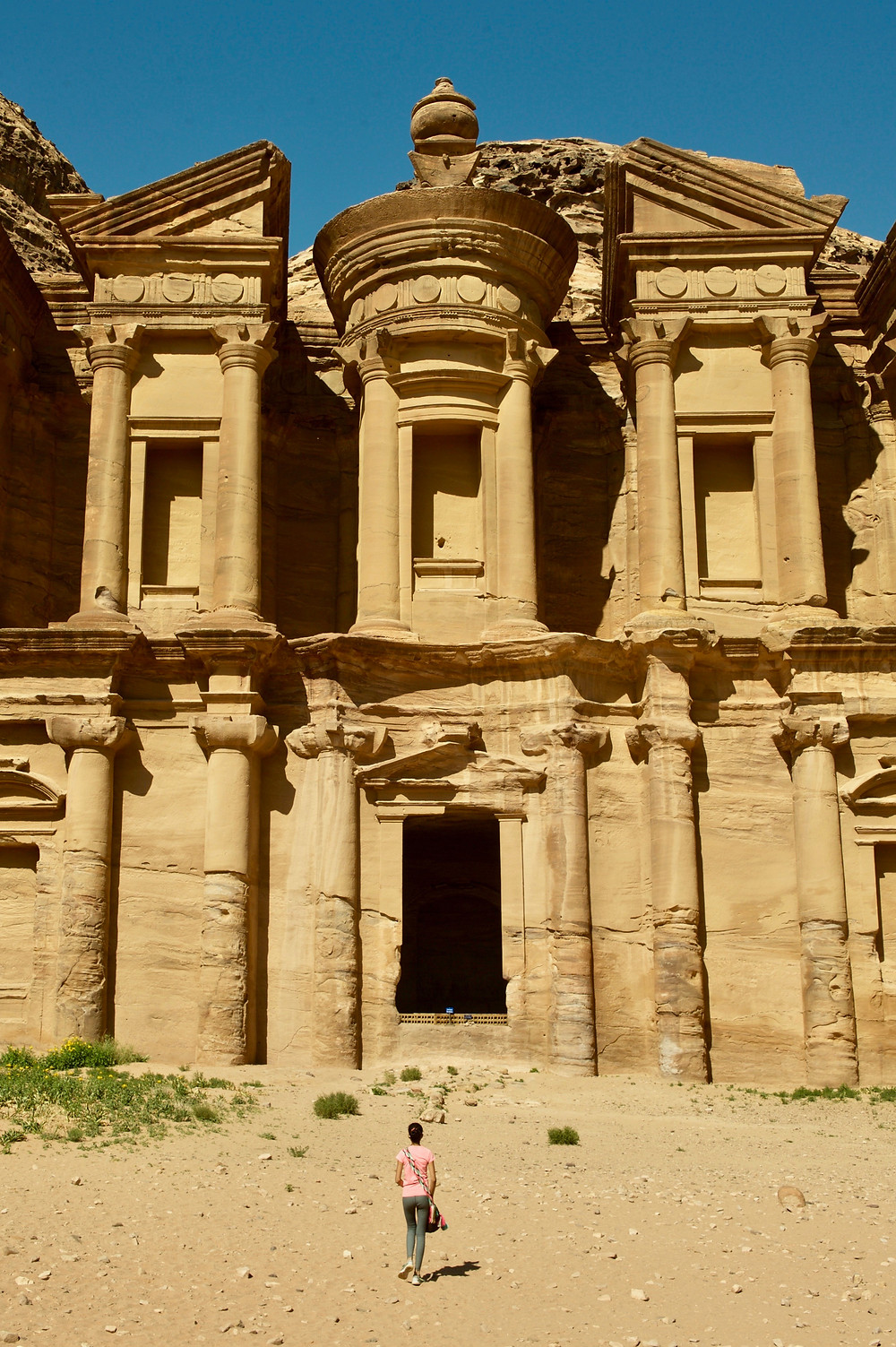 Eryn is dwarfed by the Monastery as she walks toward the structure that is carved into a cliff face in Petra