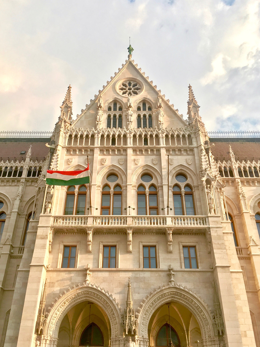 Looking up at the facade of the Parliament Building's main entrance in Budapest under a cloudy sky