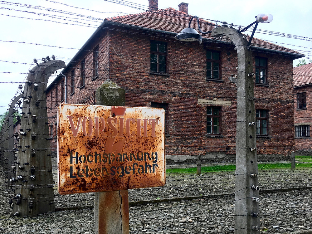 A rusted sign with German writing in front of a tall electric fence and brick buildings in Auschwitz I