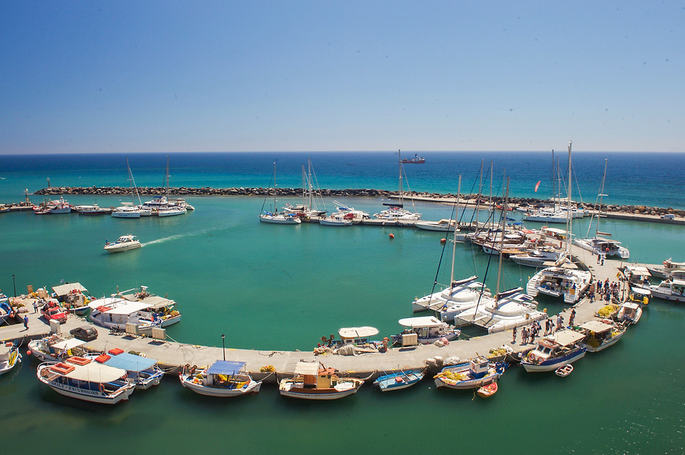 A horseshoe-shaped boardwalk lined with parked boats in turquoise water of the Vlichada Marina in Santorini, Greece
