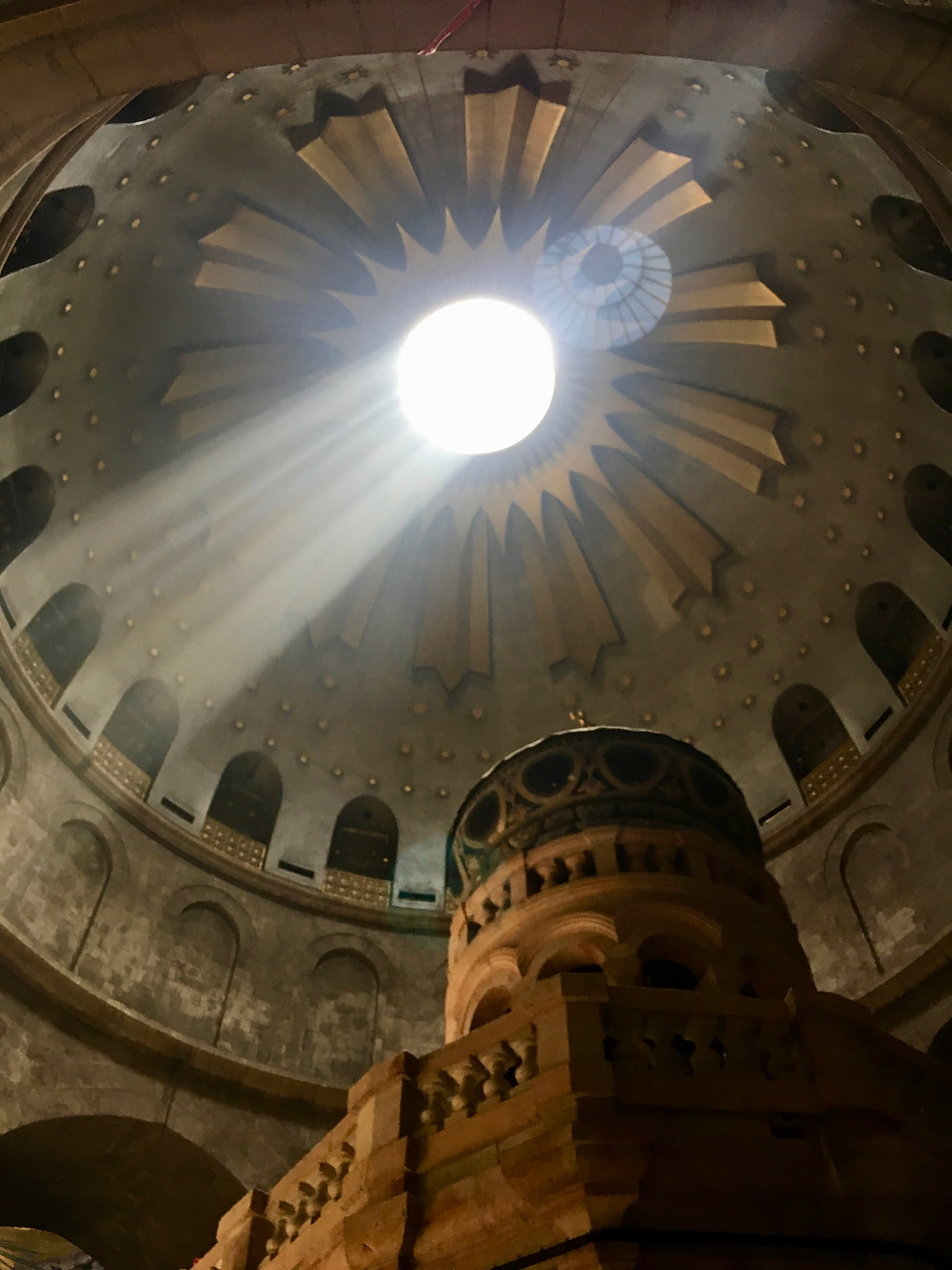 Inside the Church of the Holy Sepulchre's main dome above the Tomb of Jesus as light leaks in from the central oculus