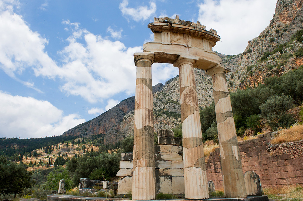 The remains of the Tholos of Delphi with the mountainous scenery of Delphi in the background