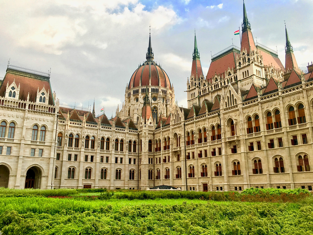 The Hungarian Parliament Building with its red roof and intricate facade under a partly cloudy blue sky in Budapest