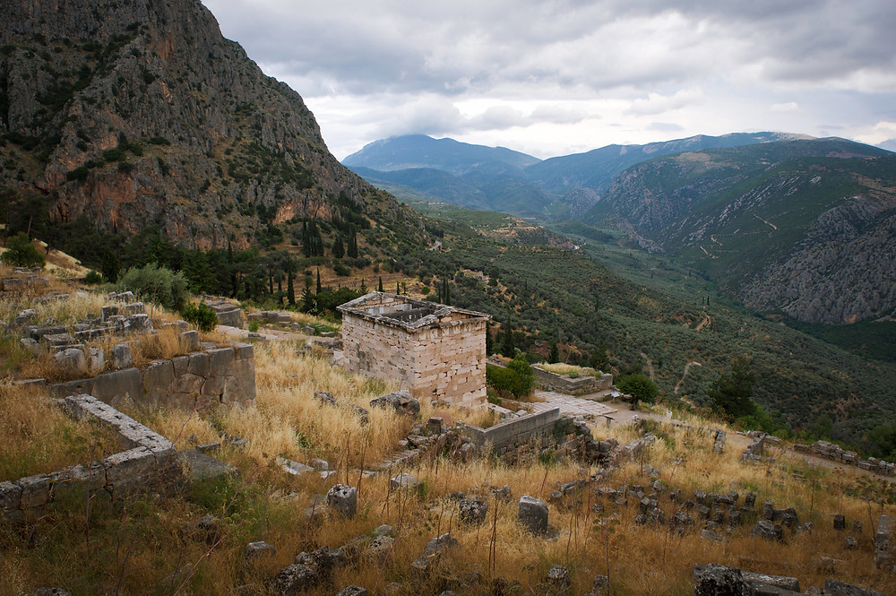 The Athenian Treasury amid the mountains and scenery of Delphi, Greece