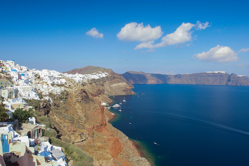 Whitewashed buildings of Oia, Santorini fringing the cliffs of the island that is wrapped around a deep blue sea