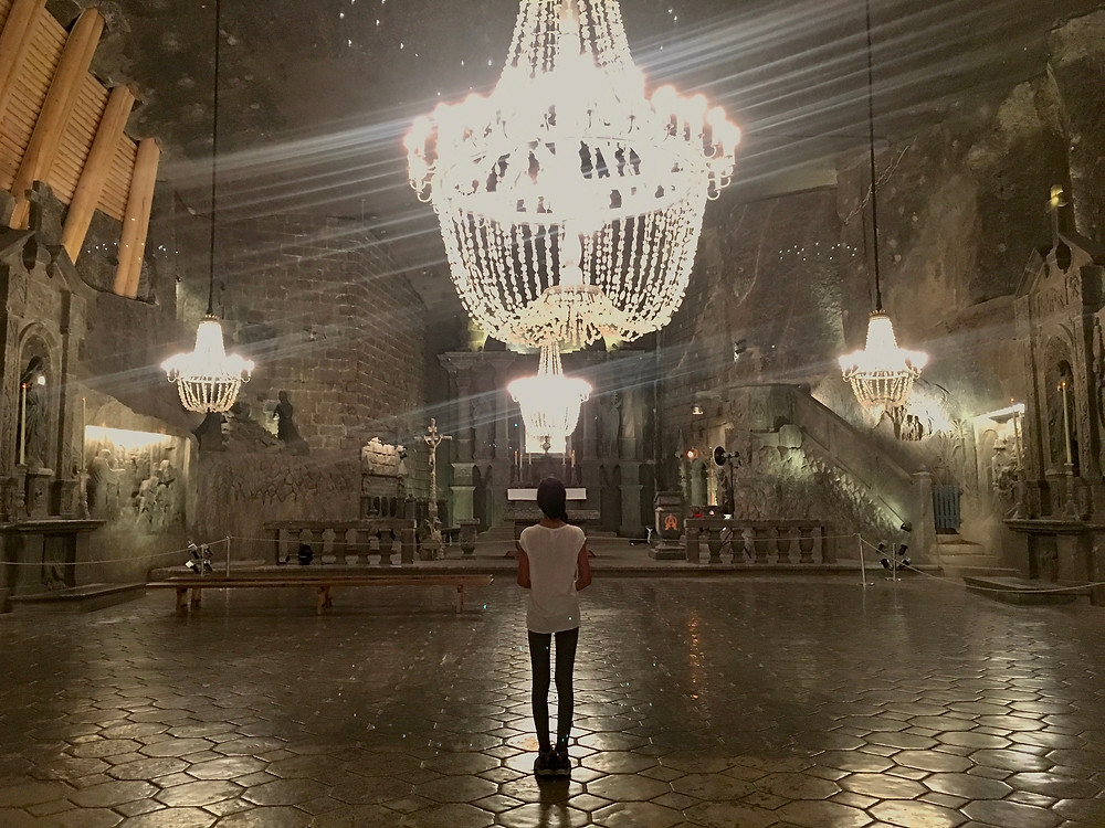 Eryn standing under one of the salt chandeliers in the St. Kinga Chapel