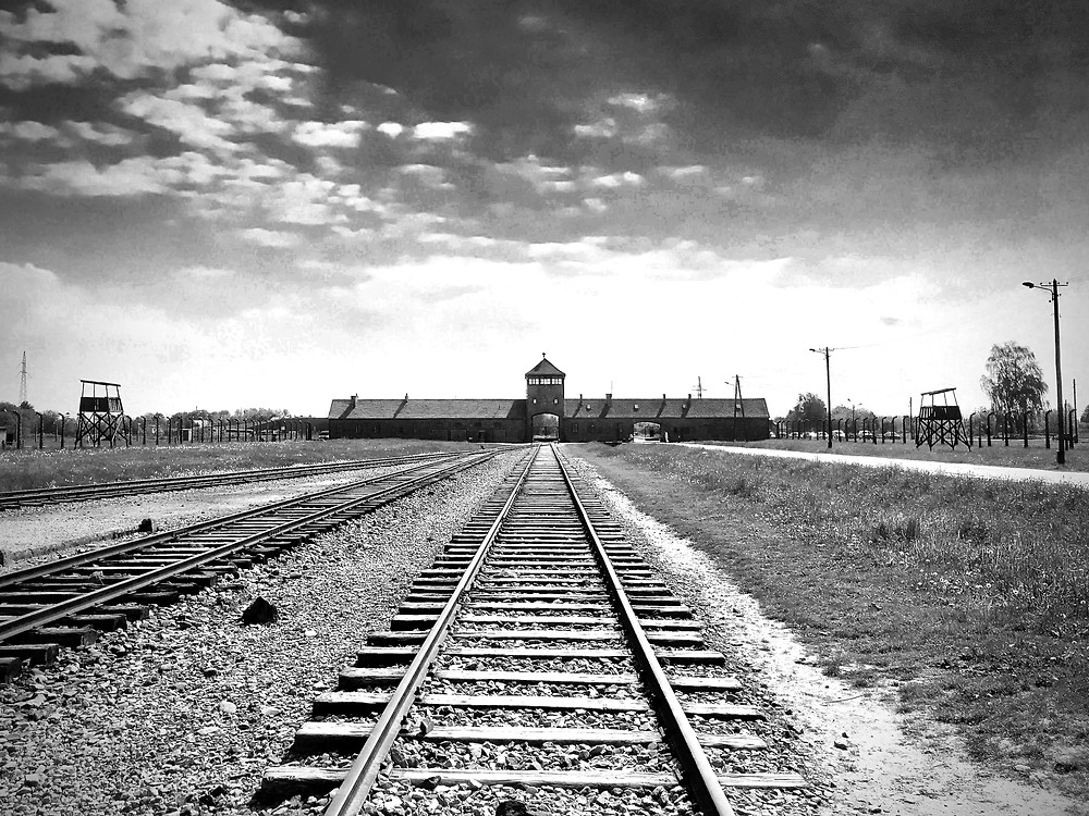 Black and white photography of railroad tracks extending through Auschwitz II's Gate of Death in the distance