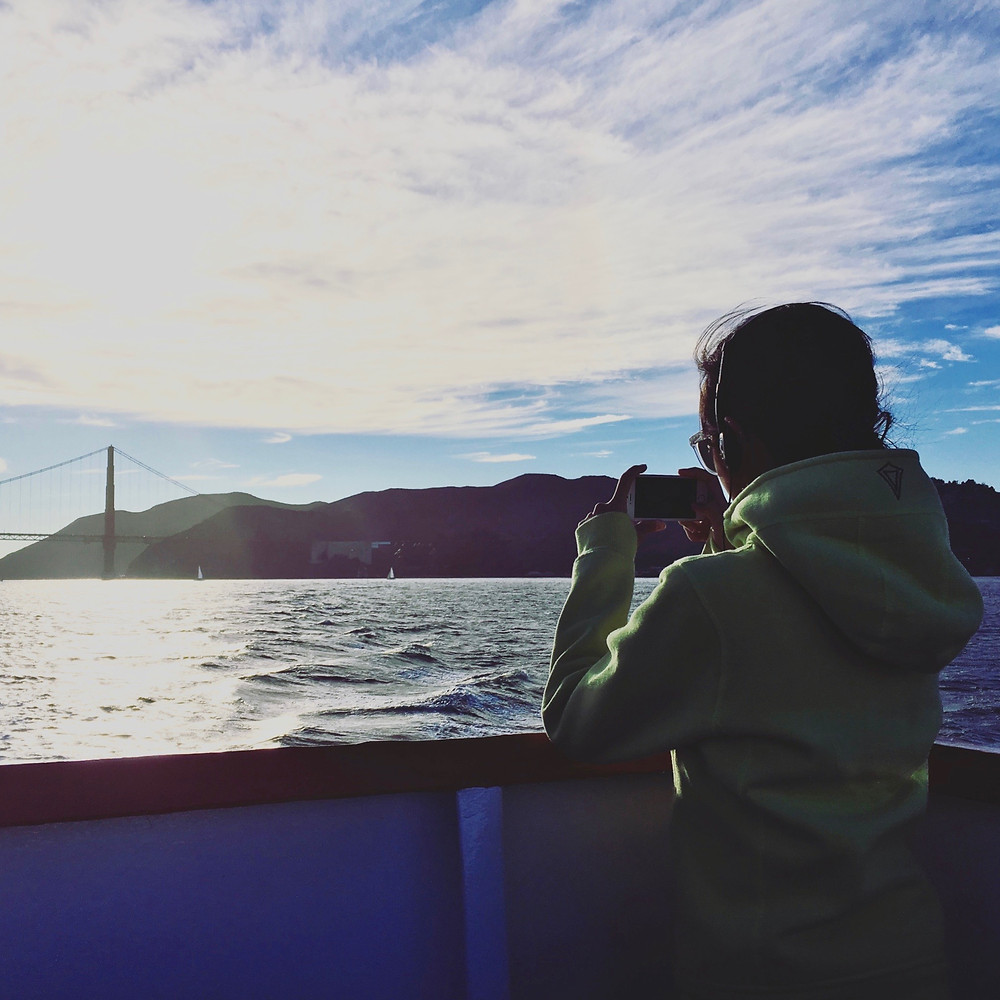 Eryn takes a photo of the San Francisco Bay Bridge in the distance from a boat