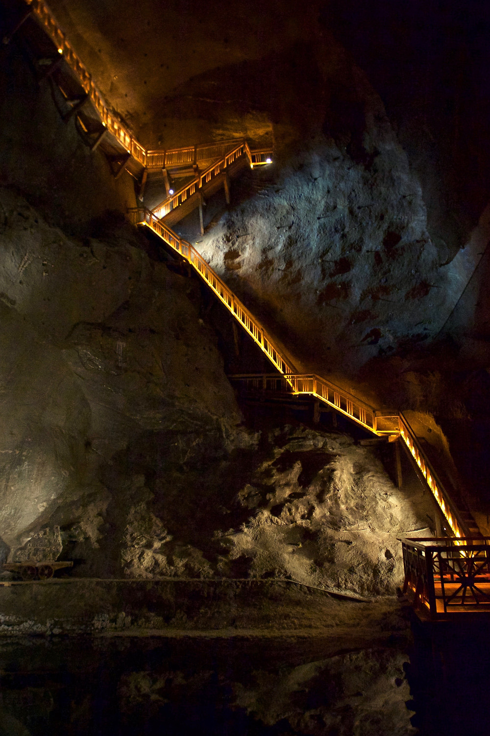 A long series of steps on the side of a salt rock face descending to a saltwater lake in the Wieliczka Salt Mine