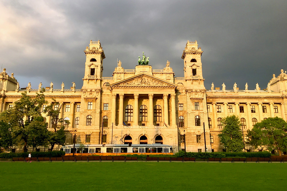 A tram passing the front of the Hungarian National Museum of Ethnography under dark grey skies in Budapest