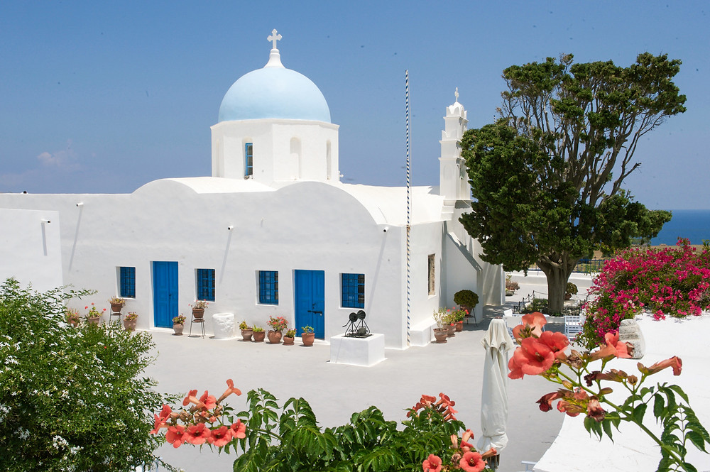 A Santorinian church building with a blue dome amid whitewashed architecture and greenery in Santorini, Greece