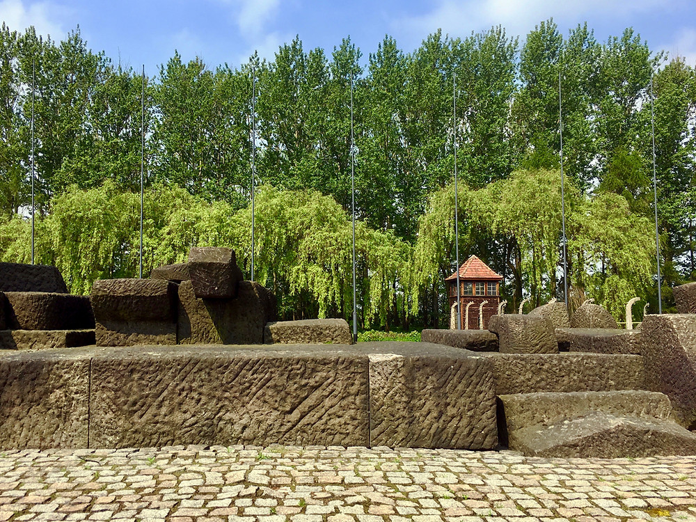 Artistic stone blocks making up a monument in Auschwitz II with a guard post surrounded by trees in the distance