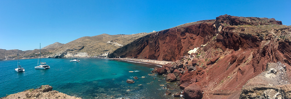 Red slopes and cliffs open to a bay of turquoise water with some small boats nearby