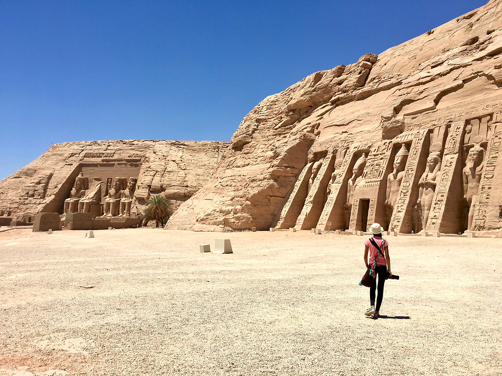 Eryn walking under a cloudless blue sky toward the two Abu Simbel temples in the distance in Egypt