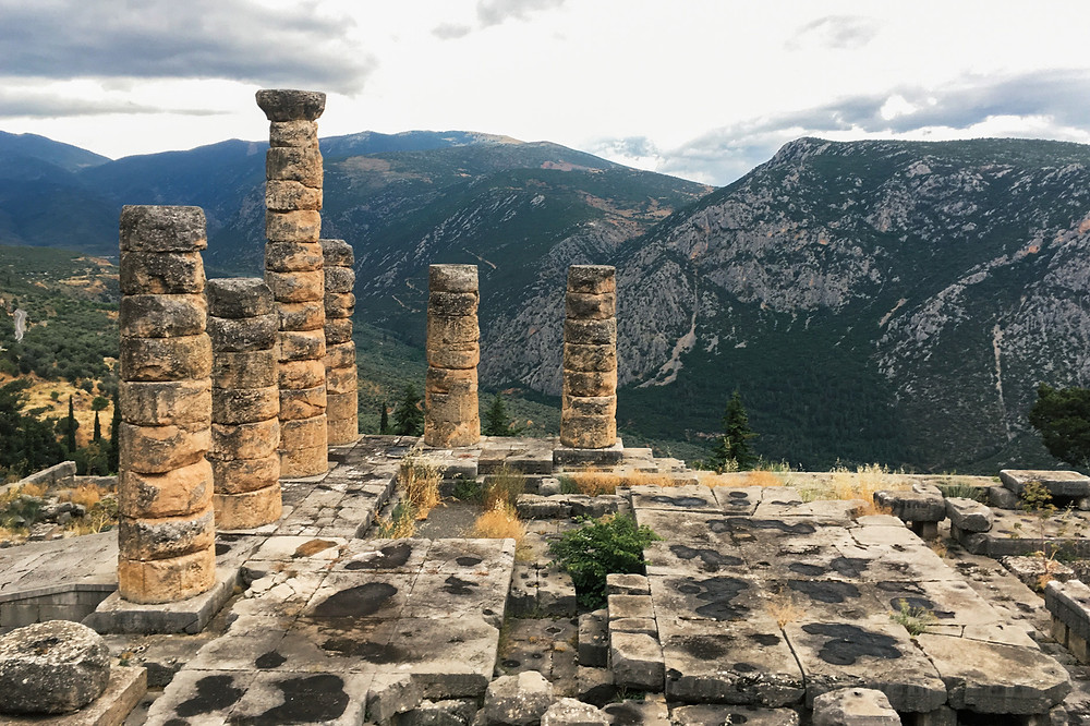 Ruins with a foundation and a few worn pillars before a green mountain range in the distance