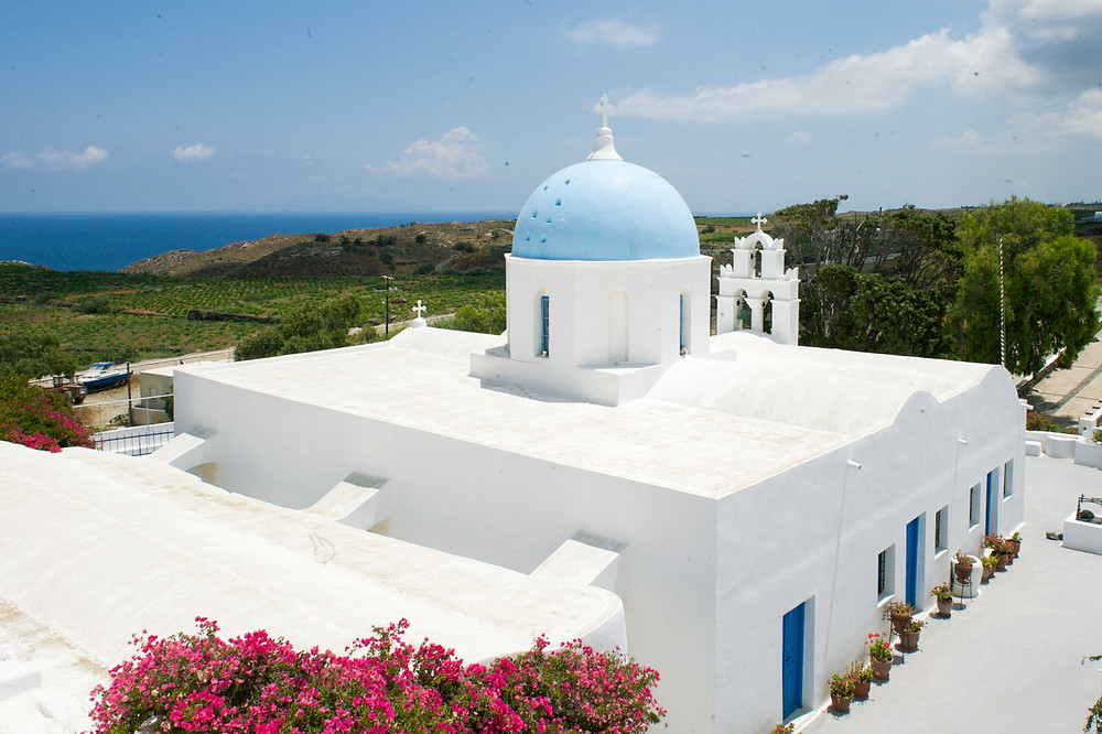 The whitewashed structure of the Aghios Artemios church with a Santorinian blue dome