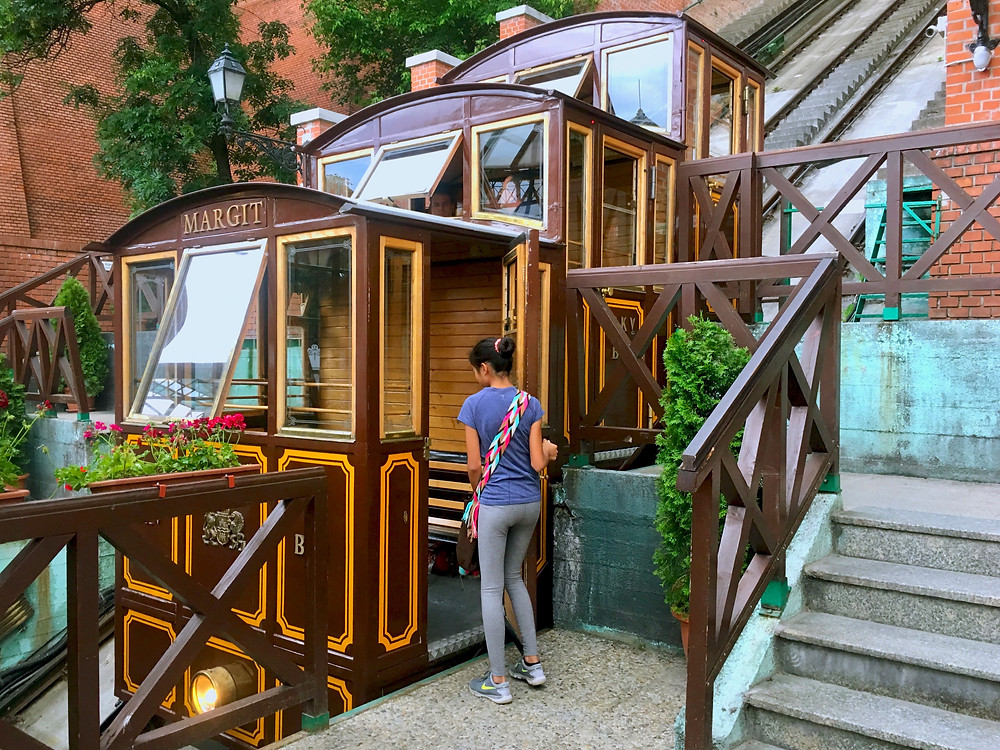 Eryn opening the door of a the Budapest Castle Hill Funicular to step inside and make the climb up to Buda Castle