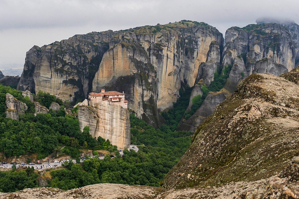 A monastery on a small pillar in front of tall cliffs in Meteora, Greece