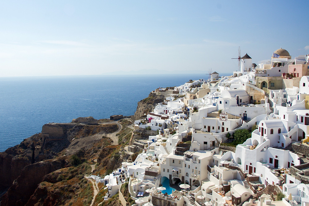 Whitewashed Santorinian buildings partially covering a hillside before the sea in the distance