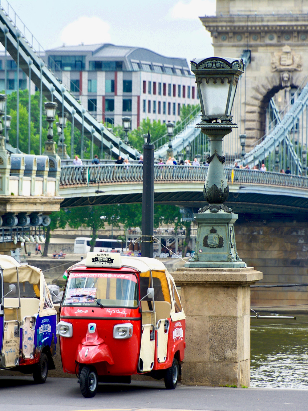 A bright red tuk tuk parked in front of a lampost by the Széchenyi Chain Bridge in Budapest, Hungary