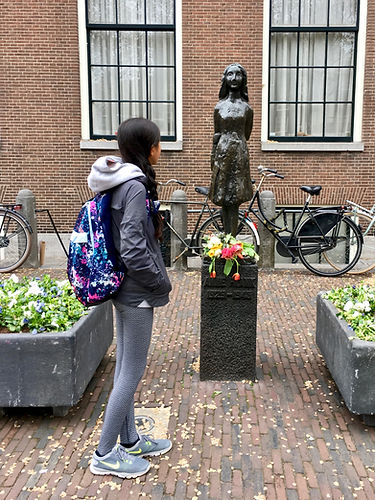 Eryn stands in front of a statue of Anne Frank in Amsterdam, the Netherlands