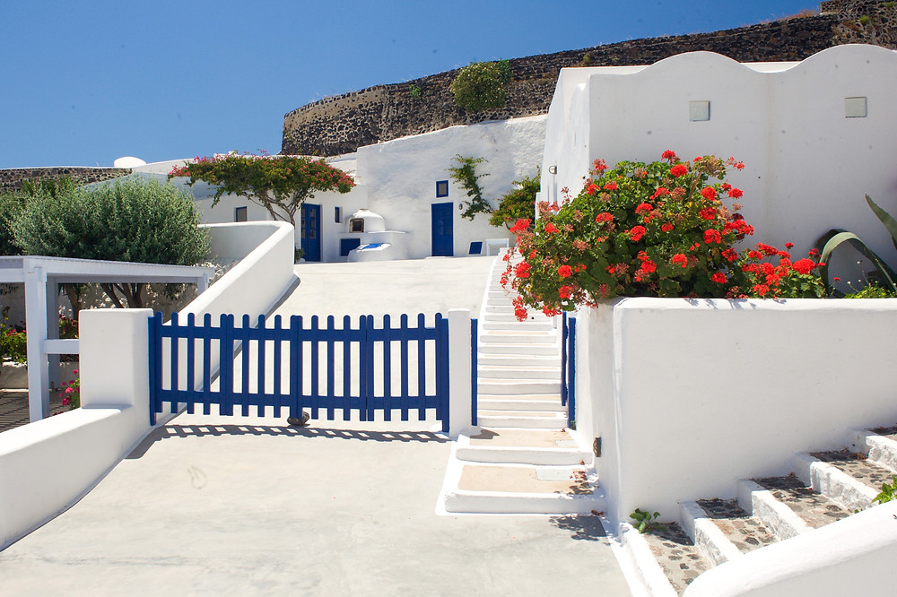 The whitewashed architecture of traditional cave houses surrounding a driveway in Aghios Artemios Traditional Houses, Santorini, Greece