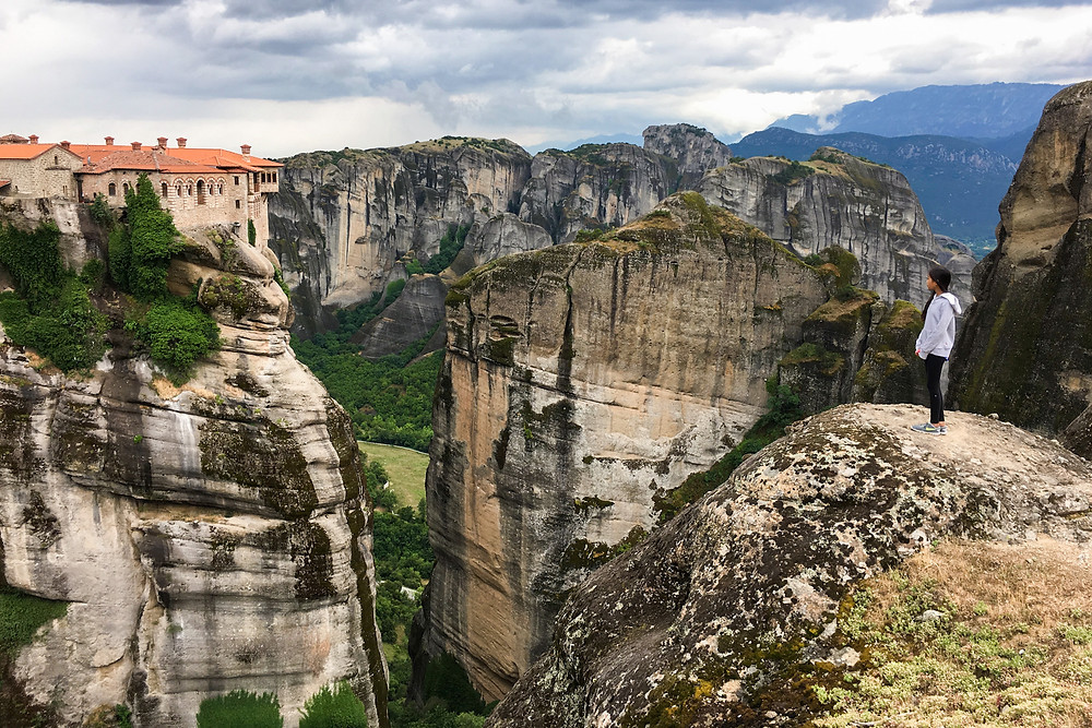 Eryn stands on a cliff and looks out to one of the monasteries in Meteora, Greece