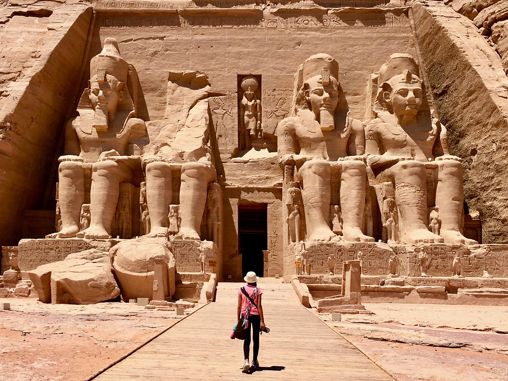Eryn following a path toward the entrance to the Abu Simbel temple where two towering statues of its pharaoh sit on either side
