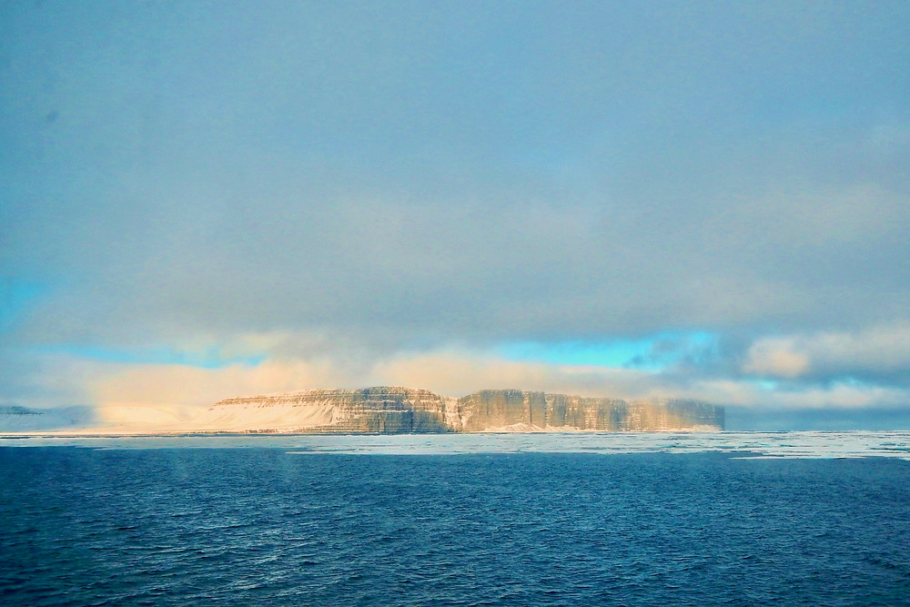 Prince Leopold Island, a flat cliff island, surrounded by sea ice in the distance with blue skies and seas