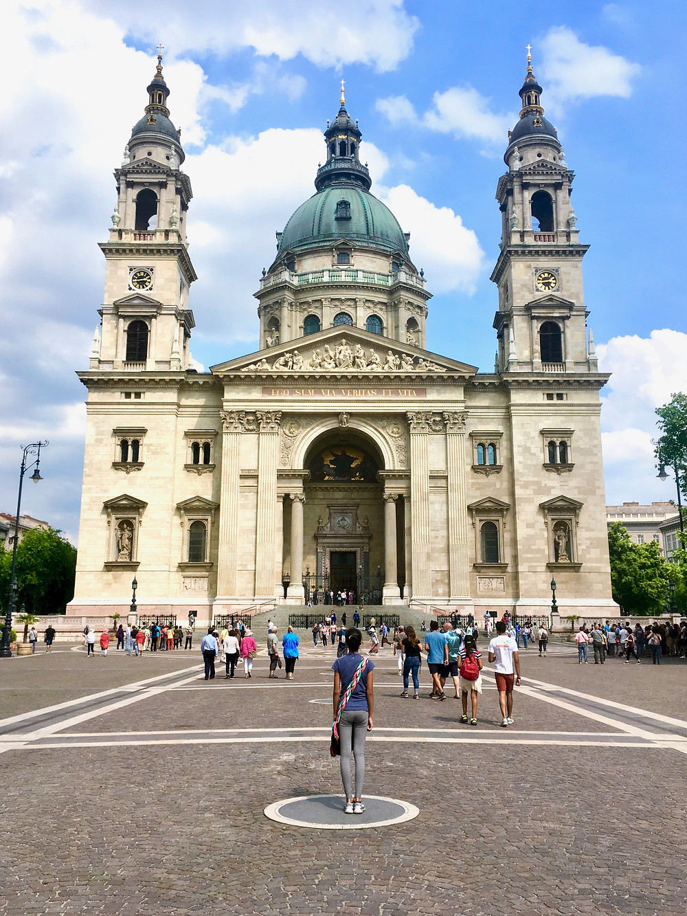 Eryn standing in front of St. Stephen's Basilica under a partly cloudy blue sky in Budapest
