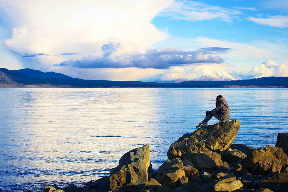 Eryn sits on a boulder and looks out to Kluane Lake in Yukon, Canada with snow-capped mountains in the distance