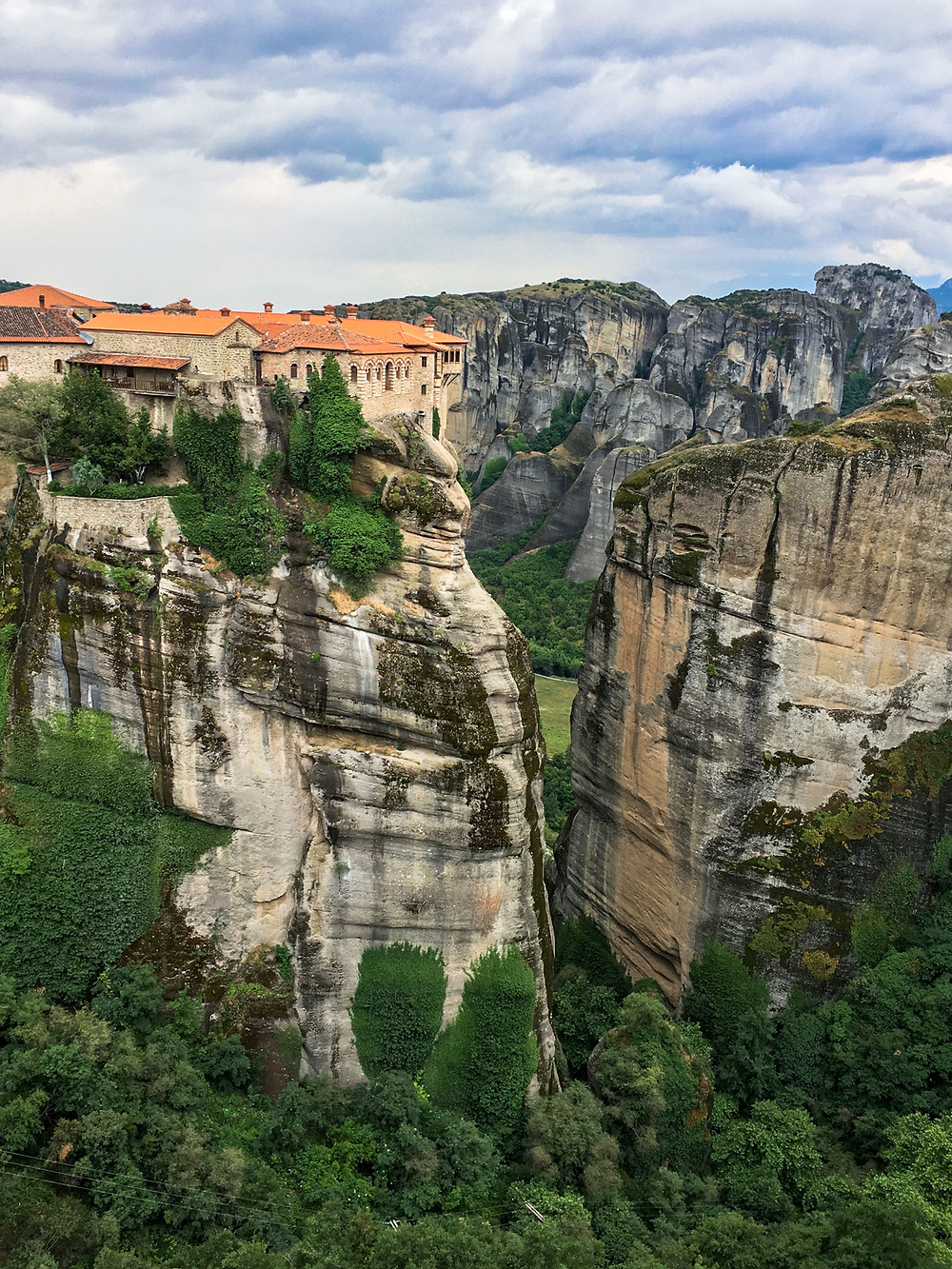 An orange-roofed monastery on a rock pillar in Meteora, Greece among the other cliffs behind and greenery below