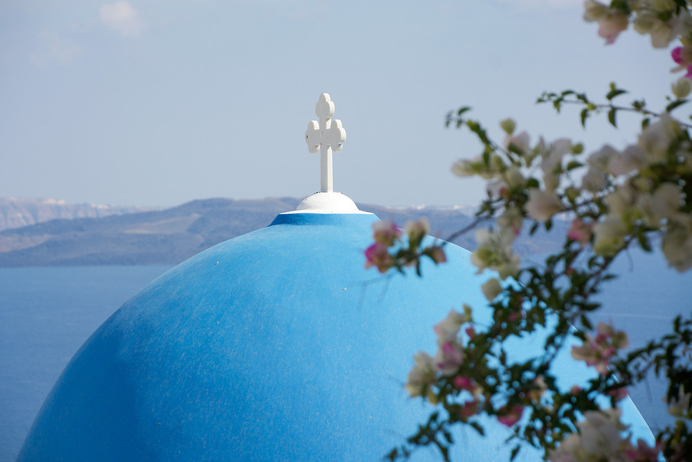 Flower branches partially cover a blue-domed roof topped with a white cross in front of ocean and the hills of an island in the distance