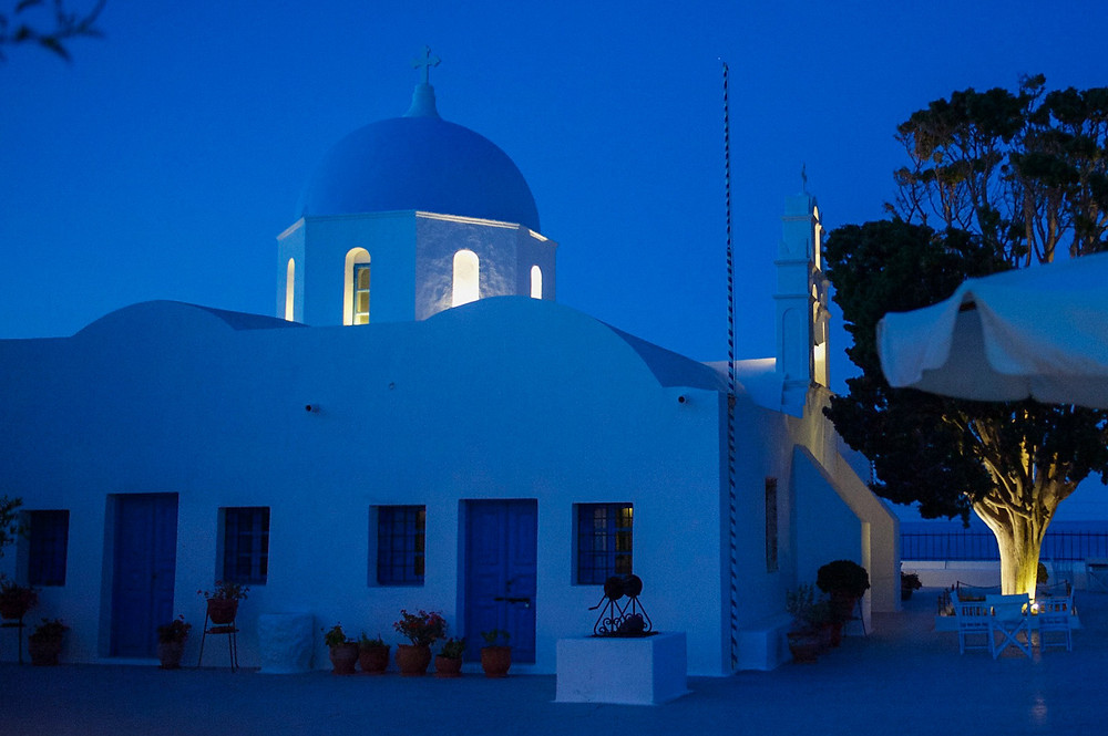 Everything turns dark blue as night sets in while yellow lights illuminate the inside of the church's blue dome and the underside of a tree in Aghios Artemios