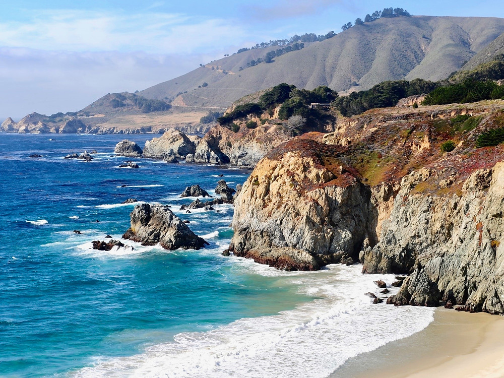 A rocky coastline in California along the Pacific Coast Highway with green hills in the distance