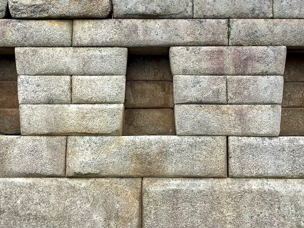 A closeup of a wall in Machu PIcchu and the trapezoidal and rectangular bricks it consists of