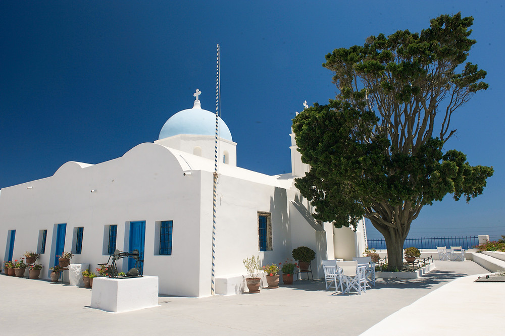 A Santorinian church building beside a large tree in the Aghios Artemios Traditional Houses grounds