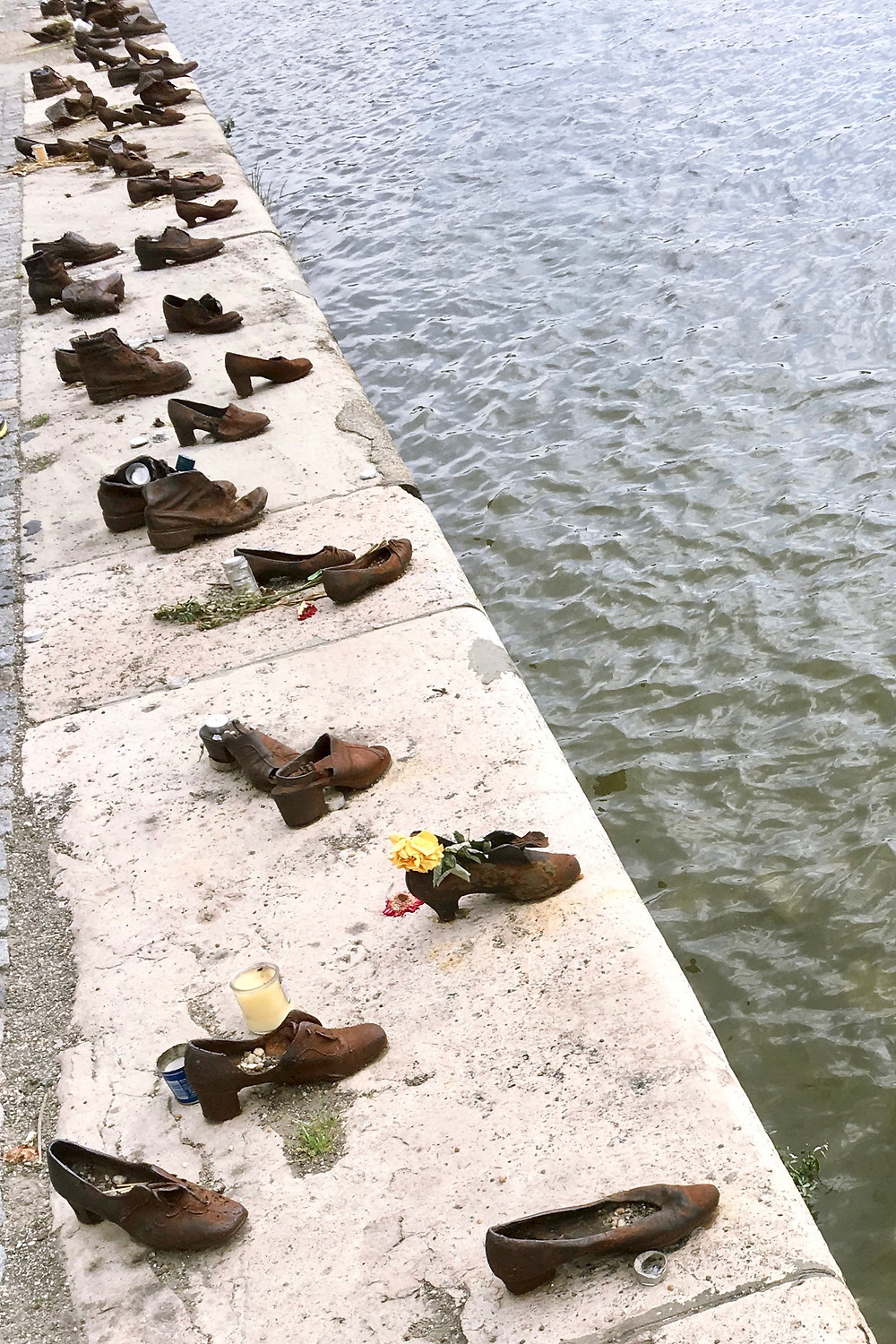 Countless metal shoes scattered at the edge of the Danube River as a part of the Shoes on the Danube Bank Monument in Budapest