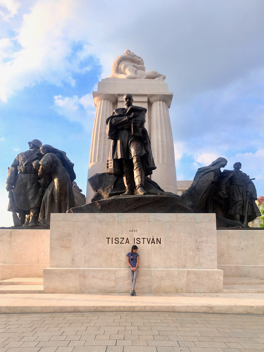 Eryn standing beneath the István Tisza Monument near the Hungarian Parliament Building under partly cloudy skies in Budapest