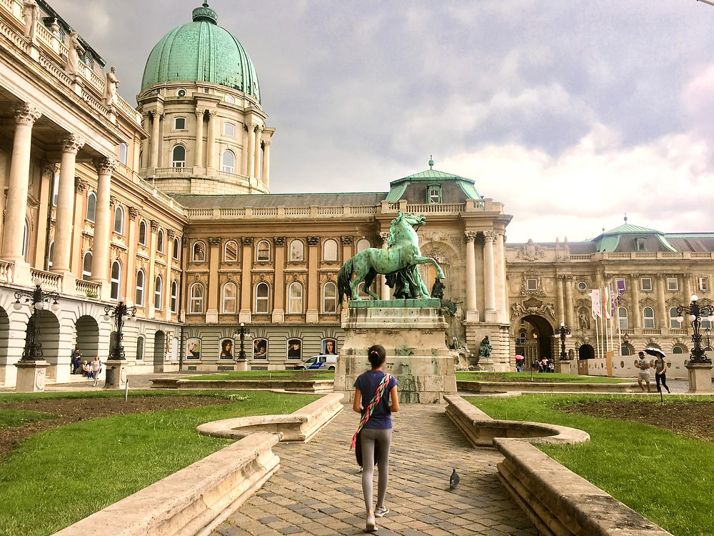 Eryn walking toward a turquoise statue of a horse before the yellow-walled, turquoise-roofed Buda Castle in Budapest